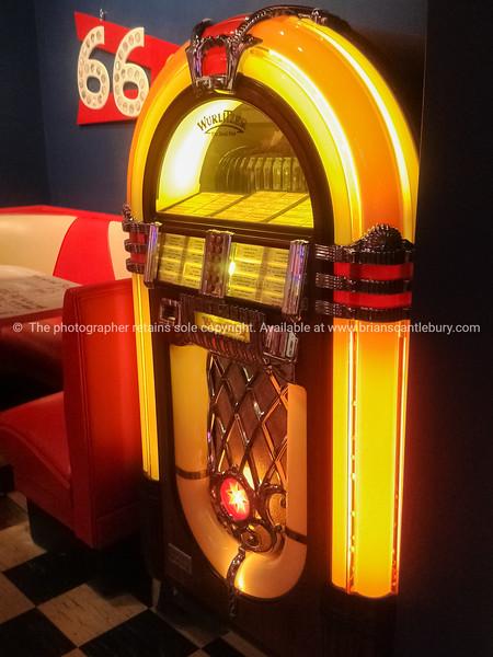 bright retro jukebox beside Route 66 illuminated sign