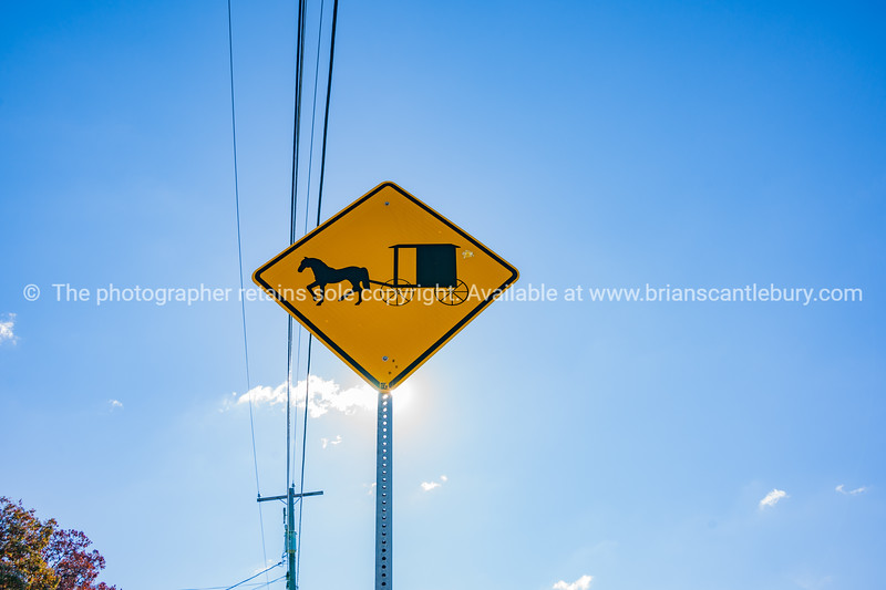 Sun shines from behind Amish traditional horse and buggy road sign in Lancaster County Pennsylvania, USA