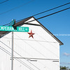 Red Mennonite star of exterior of simple white building by Temperance Hill Road street sign