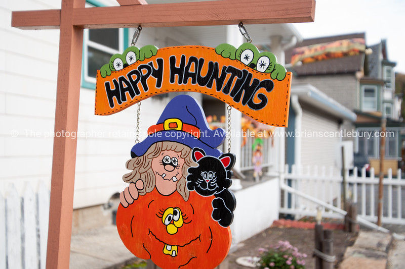 Happy Haunting halloween themed sign in front of home in street in small town USA.