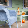 quaint front porch on street with blue wicker chairs and halloween decorations