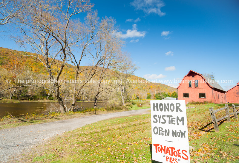 Honor system sign in rural New England beside an American style red barn by a river.
