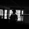 Amish farmer in silhouetted and unrecognisable milking shed, Lancaster County, PA.