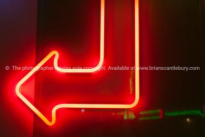 Red neon arrow on dark background.