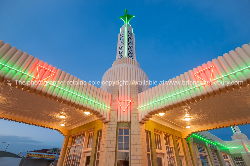 Beautiful example of art deco commercial buildingat dusk with bright neon signage.