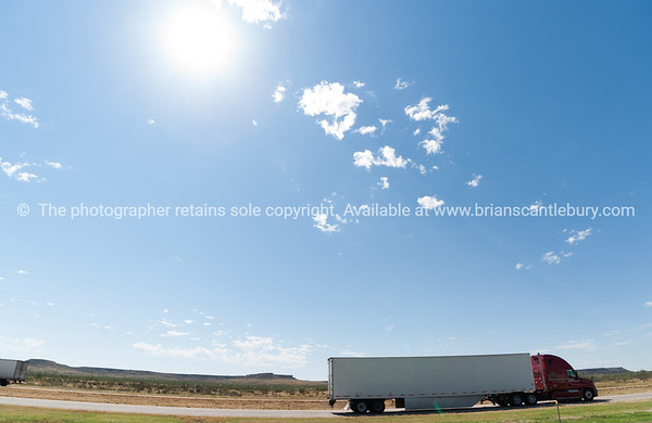 Trucks passing, mesa landforms on horizon beyond Landscape along I 40, Route 66, just out of Adrian,  Texas, USA.
