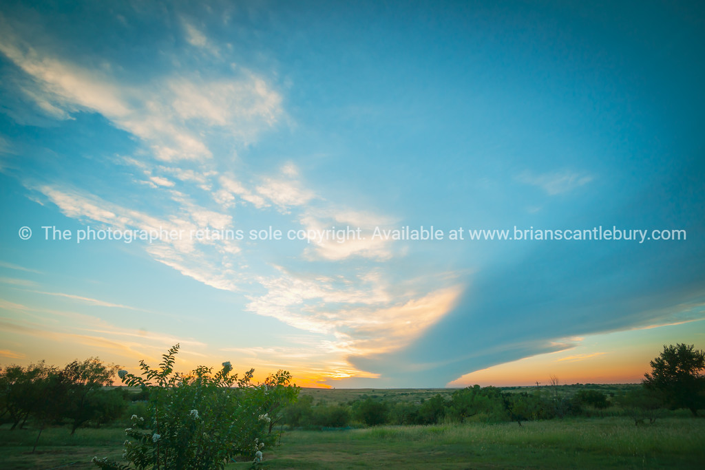 Shelf cloud spans over Texan landscape at sunset.