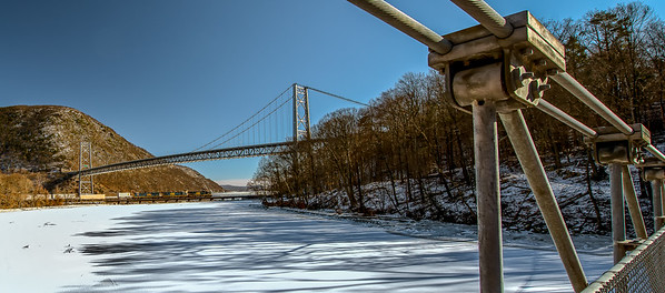 Train convoy near the Bear Mountain Bridge and a frozen tributary to the Hudson River