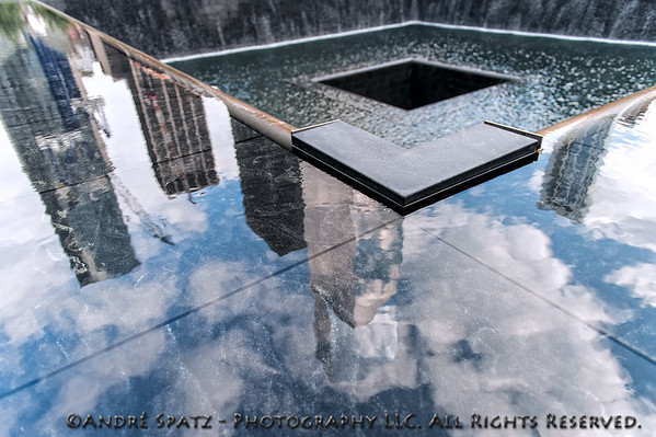 Reflections of the buildings surrounding  the 9/11 Memorial Pool