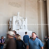Tourists blurred in motion below large white statue of Abraham Lincoln in Lincoln Memorial.