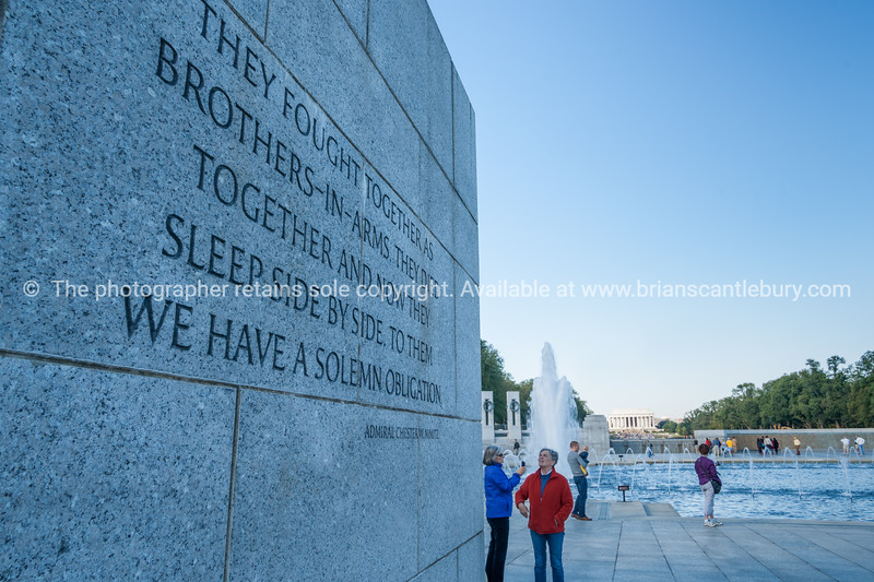Tourist reading quote engraved in stone wall  starting They fought together, at National Mall monuments.