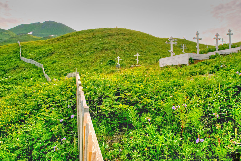 The cemetry scales up the picturesque green mountain.