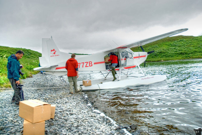 At Fraser Lake, our pilot Kyle unloads packages for one of the semi-permanent residents of Fraser from the Fisheries Dept.. The lake functions as a salmon-counting outpost. The salmon-counter guy lives on Fraser & gets supplies once a week on float planes.  So his newspaper's a week old, and sometimes two :)