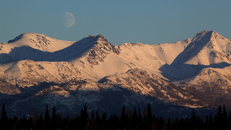 The moon slowly rises over the mountains.