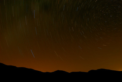 © Joseph Dougherty. All rights reserved.   Star trails above the mountains of eastern San Diego County.  The distant lights of San Diego glow on the horizon behind the hills.