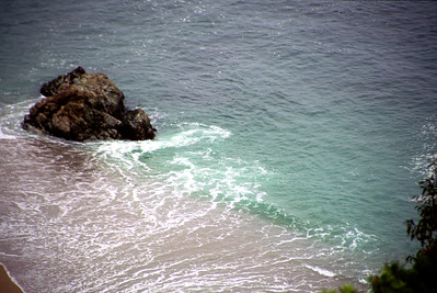 © Joseph Dougherty. All rights reserved.  Small riptide developing around a rock as waves wash off the shore.