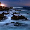 © Joseph Dougherty. All rights reserved.   A  full moon lights the rocks at the edge of Monterey Bay and gives the waves a ghostly appearance.