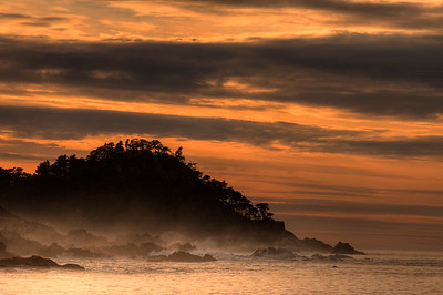 © Joseph Dougherty. All rights reserved.  Sunset over breaking waves and rocky coastline.  Point Lobos State Park, California.