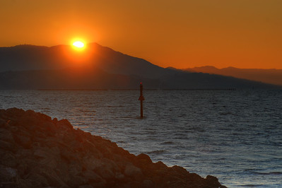 © Joseph W. Dougherty. All rights reserved.  Setting sun behind Mt. Tamalpais, over the East Bay waters and a marina return channel marker.