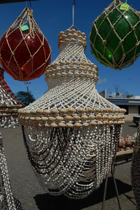 © Joseph Dougherty. All rights reserved.   Glass fishing floats and decorative sea shell lampshades for sale.   Roadside curio stand near Haleiwa, north shore of Oahu.