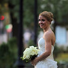 A bride, captured in a candid moment, poses in the park downtown.