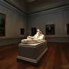 A marble nude lies oblivious to the paintings staring at her.