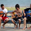 Three rather talented musicians practice their songs on the boardwalk.
