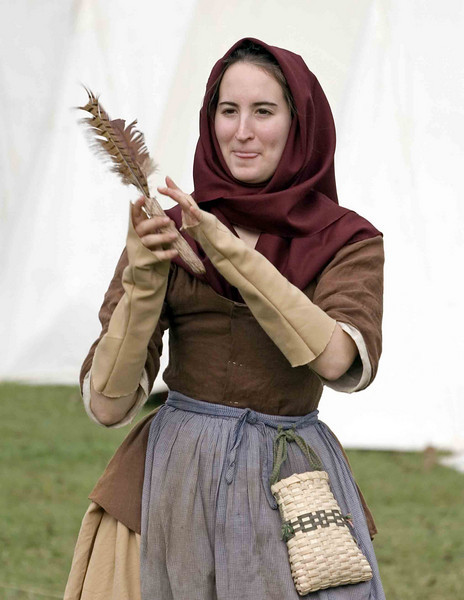 Celebration of the Victory at Yorktown 2006. Young lady playing in the American encampment.  Notice the corn cob with a feather