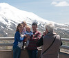 A family has it's photo taken in front of the mountain.
