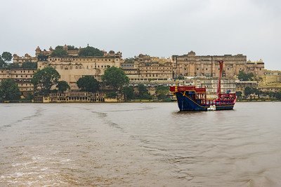Traditional boat in front of City Palace, Udaipur from Lake Pichola, Udaipur, RJ, India.