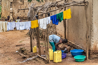 Street scene.  The large water containers are used to get water from a central source of clean water all over Uganda.