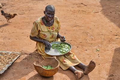 A Karamojong woman preparing some of the vegetable she has harvested for the family dinner.