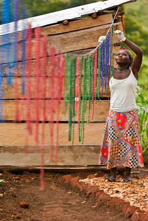 harriet hanging up beads to dry after applying shellac at her home in the village