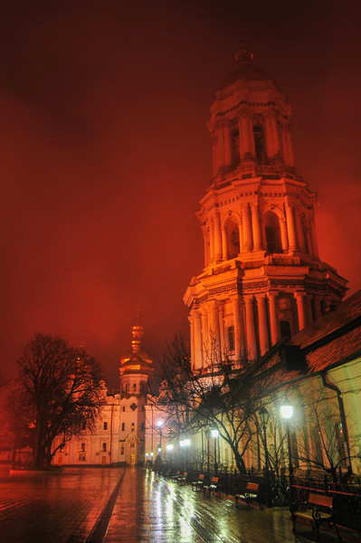 View of Kiev Pechersk Lavra and the Bell Tower in Ukraine at night, enveloped in fog. The orthodox monastery is included in the UNESCO world heritage list.