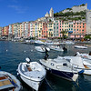 The port and old town of Portovenere.  The houses built solidly adjoining one another formed a defensive wall on the gulf side while the stone gate and wall up the mountain to the Doria Castle were erected about  1161.