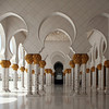 Sheikh Zayed Grand Mosque: colonnade and courtyard... white marble and palm frond capitals, gleaming under a midday sun.