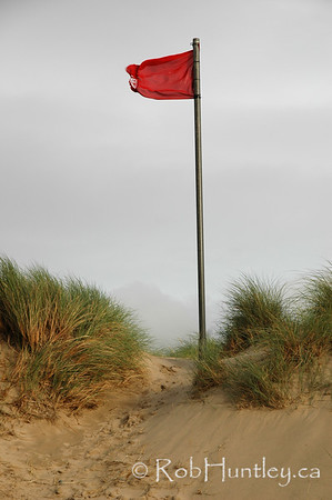 Red danger flag on a beach. Warning flag at the top of a grass-covered sand dune indicating unsafe swimming conditions. © Rob Huntley
