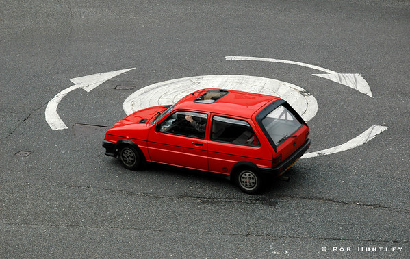 Red Car in Roundabout. A traffic circle, Conwy, Wales. Taken from the wall of Conwy Castle.  See a TinyTown adaptation of this image. © Rob Huntley