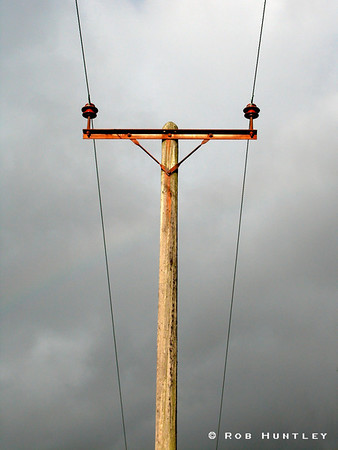 Telephone and wires centred against a grey stormy sky.