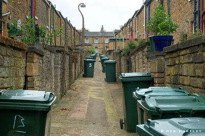Garbage day. Back alley with garbage bins in the town of Saltaire, England. HDR - high dynamic range image. © Rob Huntley