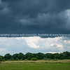 Dark storm clouds above horizon and green field