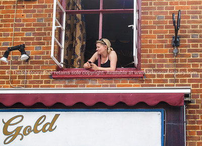 """Girl in the window, above shop sign """"Gold"""". Model released; no, for editorial & personal use. SEE ALSO:  www.blurb.com/b/893070-impressions-of-the-uk"""