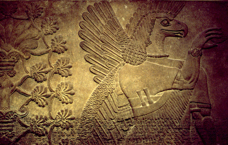 Wall relief depicting Assyrian winged deity, with cuneiform inscription across the base. From the collection of the British Museum, London.