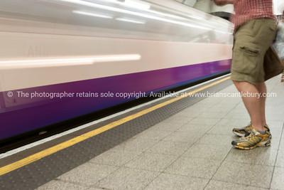 Blurred image of man as train arrives at platform.