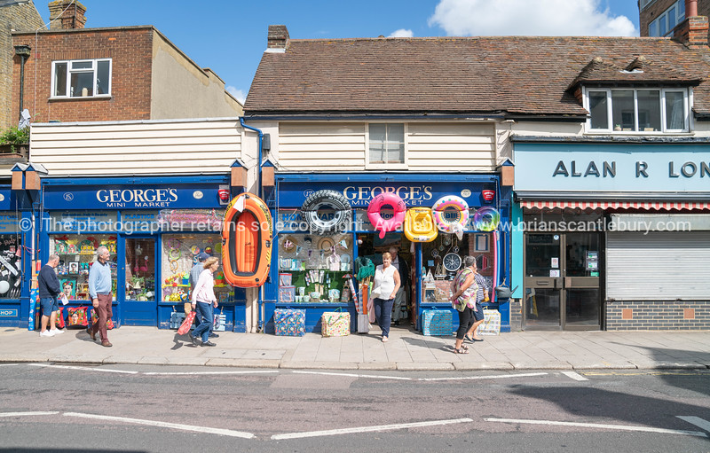 People passing Georges Mini Market with beach toys displayed on High Street.