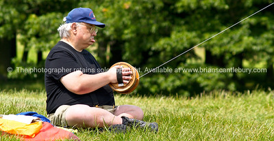 Kite flying, man sits concentrating on holding his kite string reel. Model released; no, for editorial & personal use. SEE ALSO:  www.blurb.com/b/893070-impressions-of-the-uk