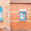 Red brick wall with two blue windows.