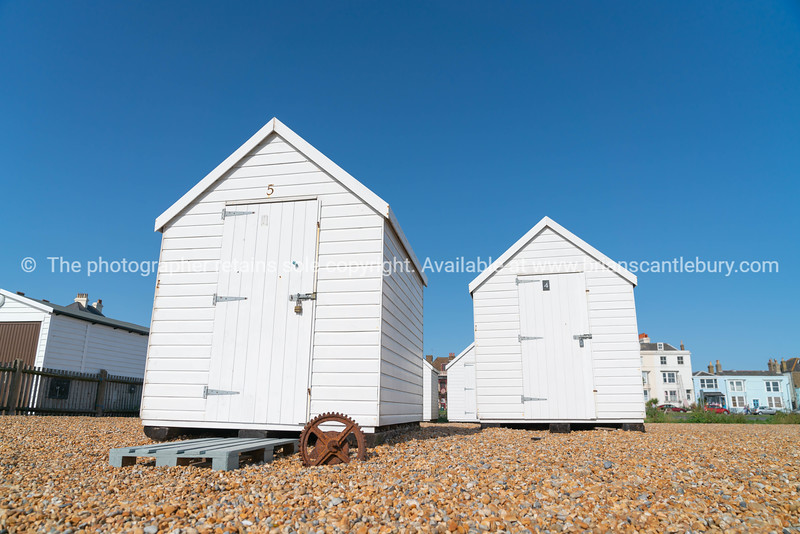Two white beach sheds on Deal waterfront.