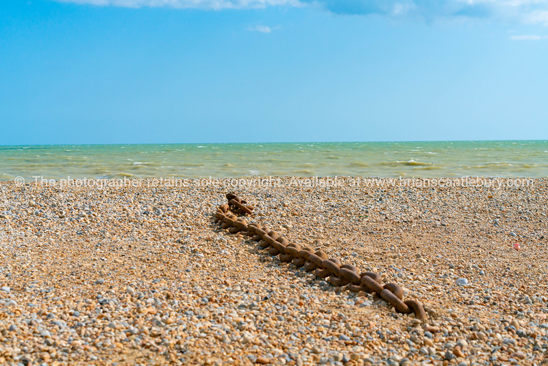 Length rusty heavy chain left lying on stony beach