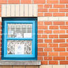 Blue window in red brick wall.